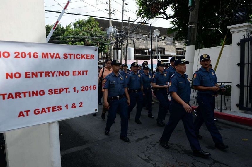Police officers walk past a gate during a house-to-house campaign on illegal drugs at an affluent neighbourhood in Manila on Sept 5, 2016.