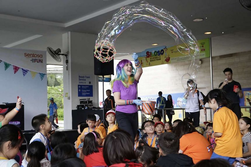"""CJ the """"Bubble Girl"""" (in purple) performs tricks with bubbles for children from voluntary welfare organisation at Beach Station in Sentosa on Sept 5, 2016."""