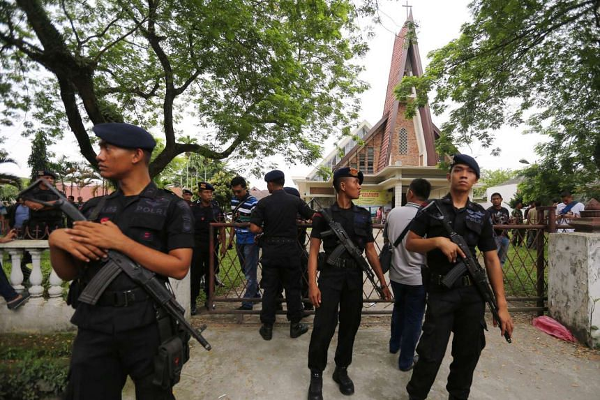 Indonesian mobile brigade policemen stand guard after an attempted suicide bombing by an unidentified man at St. Yoseph Catholic Church in Medan on Aug 28, 2016.