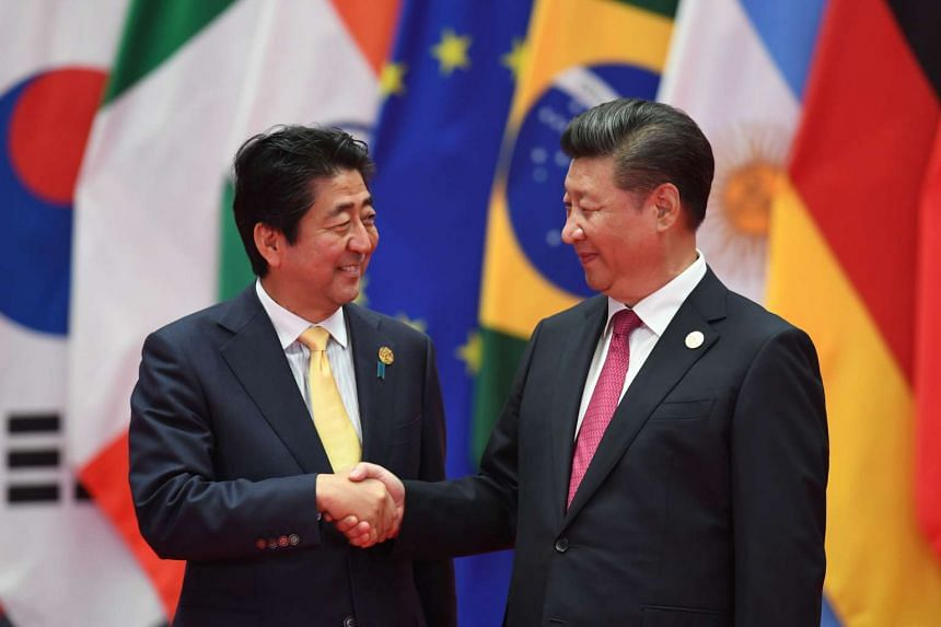 Japan's Prime Minister Shinzo Abe (left) shakes hands with China's President Xi Jinping before the G20 leaders' family photo in Hangzhou on Sept 4, 2016.