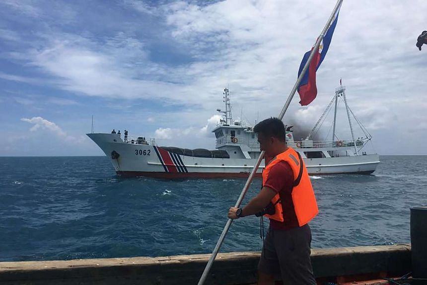 Filipino activist holding a Philippine flag while a Chinese coast guard ship sails close by their ship at the Scarborough Shoal, 230 kilometres off the main Philippine island of Luzon, in the South China Sea.