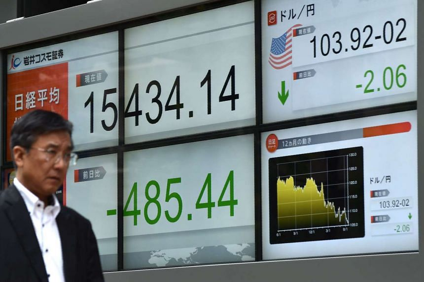 A pedestrian walks past an electronic indicator of the Tokyo stock market displayed in the window of a securities company in Tokyo on June 16, 2016