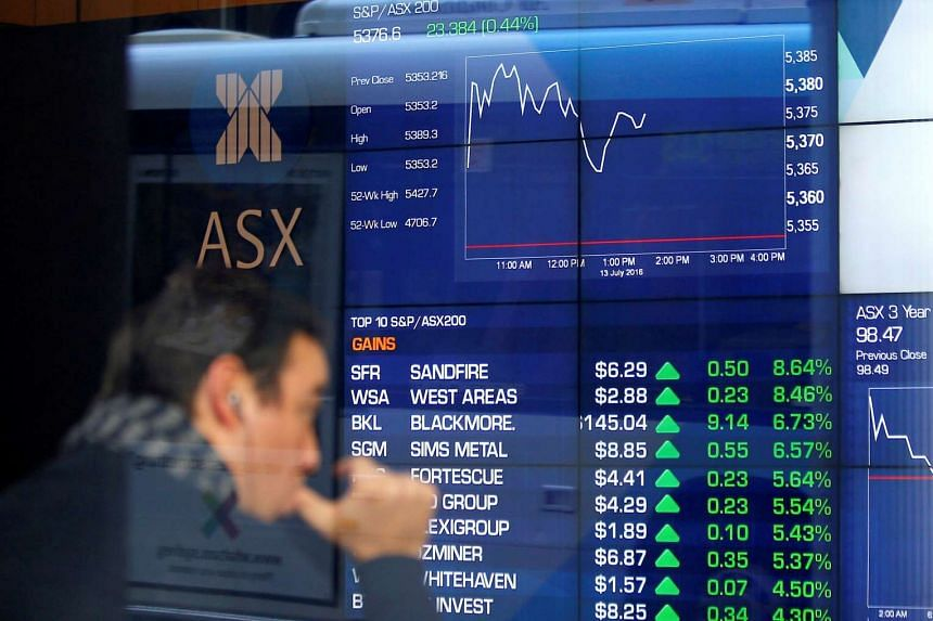 An investor reacts as he looks at a board displaying stock prices at the Australian Securities Exchange (ASX) in Sydney, Australia, on July 13.