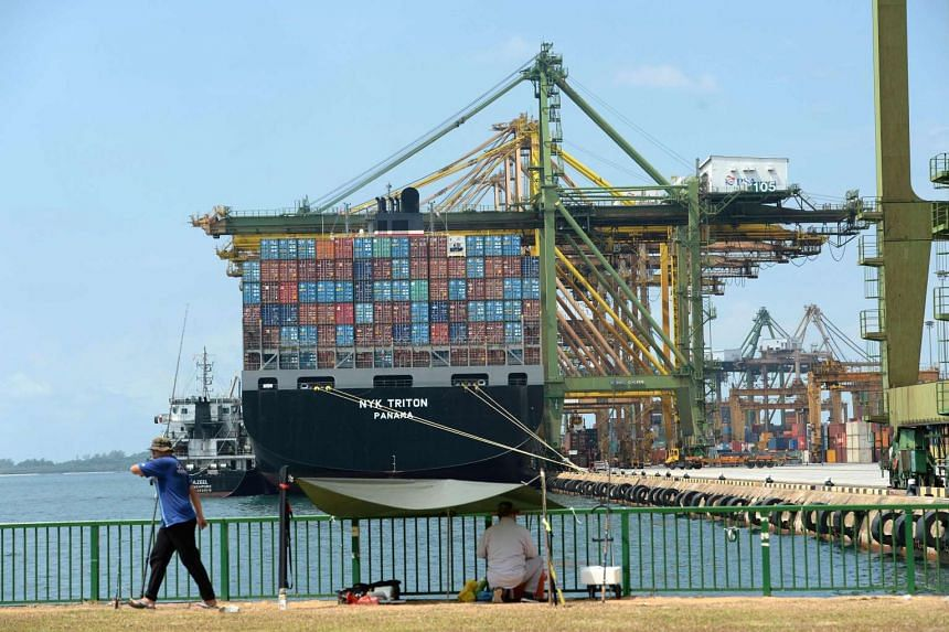 Two man fish next to a container port in Singapore on Aug 17, 2016.