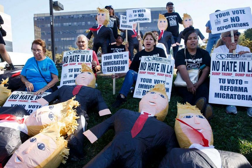 Protesters chant near Donald Trump pinatas as they encourage Latinos to register to vote against the US Republican Presidential nominee in Norwalk, California, USA on Aug 31, 2016.