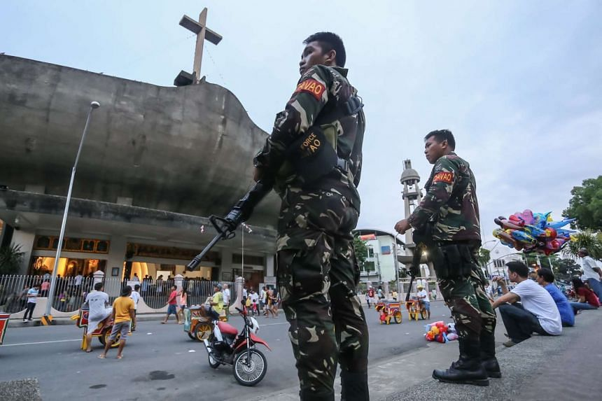 Military personnel stand guard in front of a church in Davao City, in the southern island of Mindanao on Sept 4, 2016.
