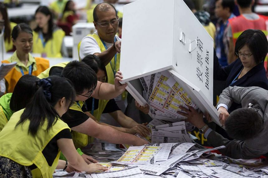 Officials empty ballot papers for the Legislative Council election from a ballot box at the central counting station in Hong Kong, China on Sept 5, 2016.