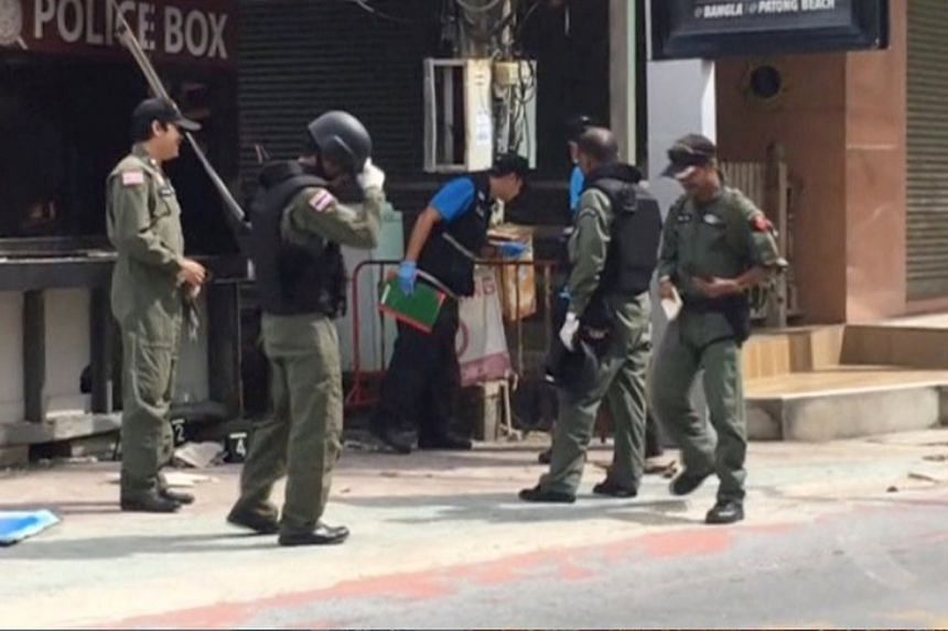 Officials investigate the scene of bomb attacks in the tourist beach town of Patong on Phuket Island on Aug 12, 2016.