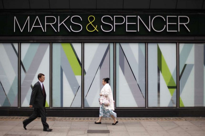 Pedestrians walk past a branch of Marks & Spencer in north-west London, Britain.