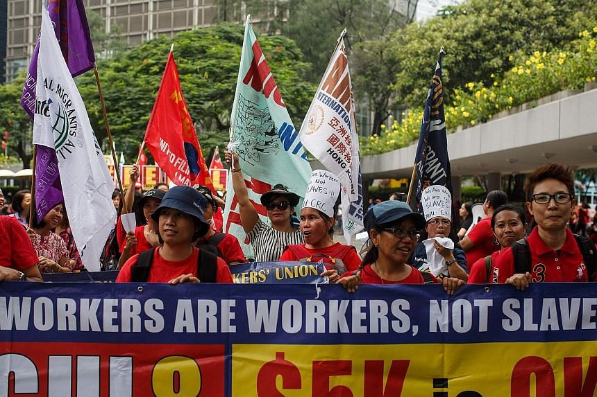 """While protesting in Hong Kong yesterday, hundreds of domestic helpers chanted: """"We are workers, not slaves."""" Rally organisers believe at least three maids have died while cleaning windows this year."""
