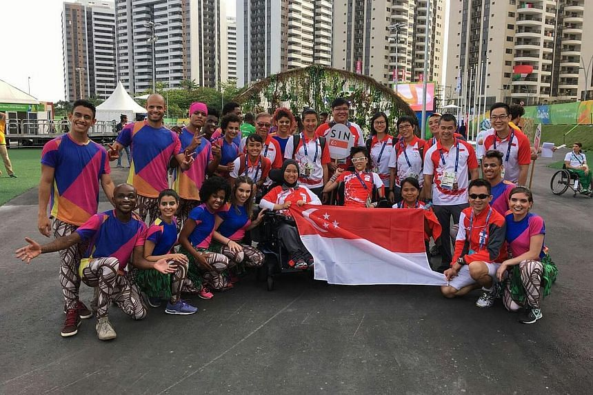 Singapore boccia athletes Nurulasyiqah Taha and Toh Sze Ning (centre, in wheelchairs) and Team Singapore officials posing for photos with Brazilian performers at the Republic's flag-raising ceremony in the Paralympics Athletes Village in Rio de Janei