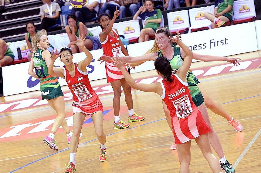 Singapore goal shooter Charmaine Soh (far left, in red) attempting to catch a ball passed by attacker Zhang Ailin. Soh scored 43 goals while debutante Zhang displayed a 100 per cent shot accuracy at the OCBC Arena yesterday.