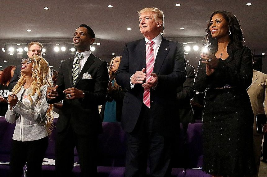 Mr Trump and reality TV personality Omarosa Manigault, director of African-American outreach for his campaign, attending a service at the Great Faith Ministries International Church on Saturday. In his first visit to an African-American church, he to