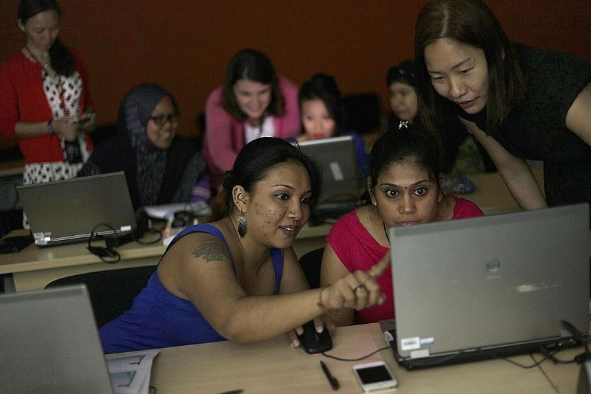 Ms Sarina (far left) and Ms Kavitha Amudhan, 38, learn how to use Excel with the help of volunteer trainer Chan Wai.