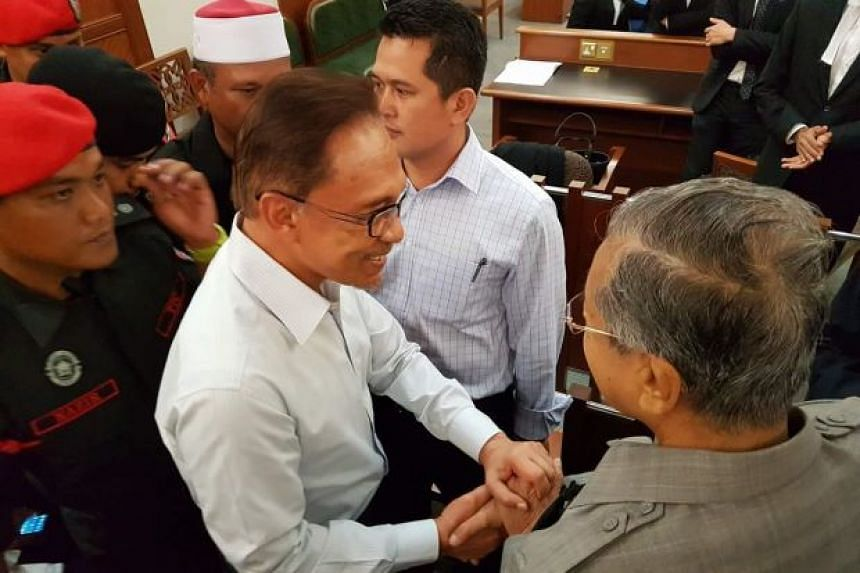 Former Malaysia PM Mahathir Mohamad (right) shaking hands with his former DPM Anwar Ibrahim at the Kuala Lumpur High Court on Sept 5, 2016.
