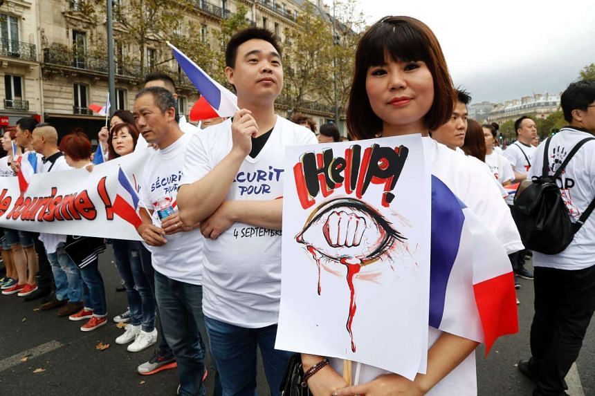 A members of the Chinese community in Paris holds a placard during a demonstration on Sunday (Sept 4) in Paris, following the death of Zhang Chaolin.