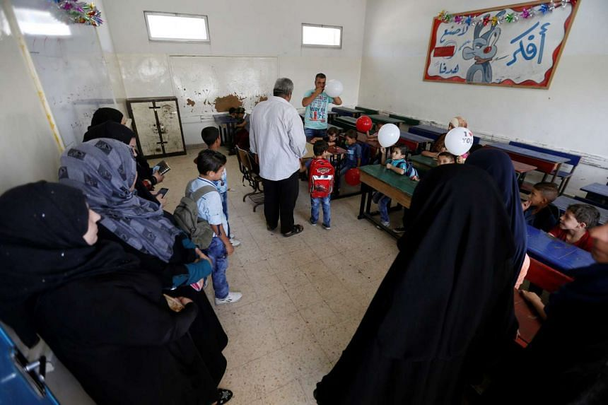 Palestinian refugee parents wait for their children at one of the UNRWA schools at a Palestinian refugee camp on Sept 1, 2016.