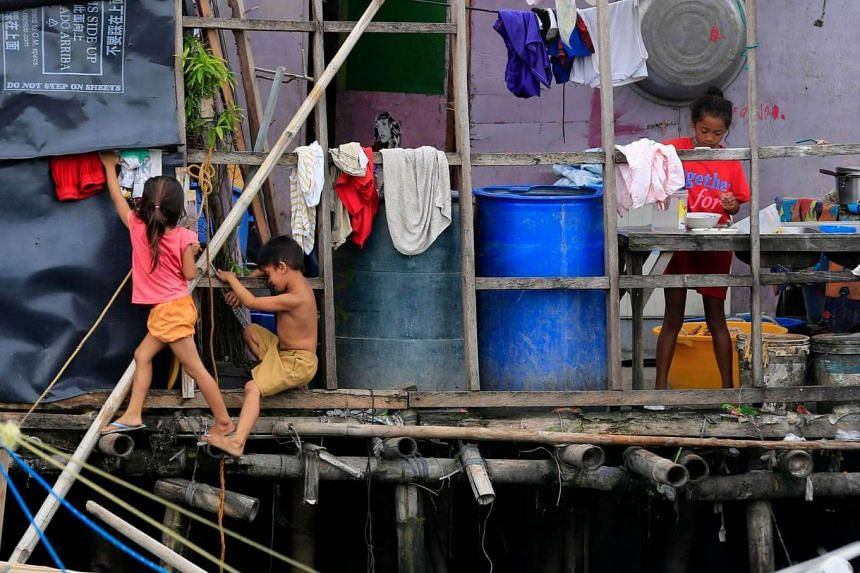 Filipino children play in shanties along a polluted river in Las Pinas city, south Manila, Philippines on Sept 5.