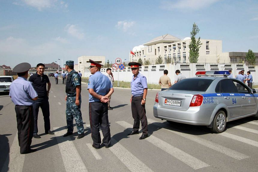 Kyrgyz investigators and security personnel gathering near the site of a bomb blast outside China's embassy in Bishkek, Kyrgyzstan, pm Aug 30, 2016.