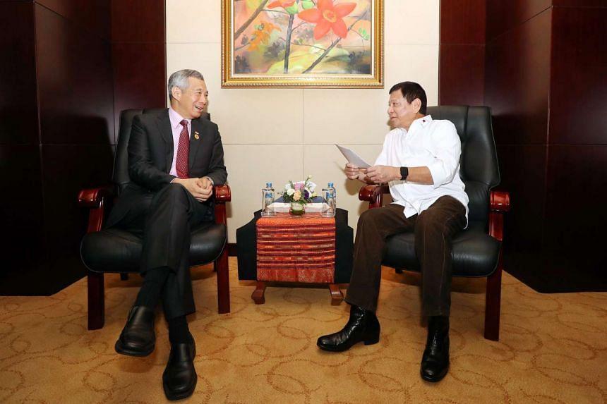 Singapore PM Lee Hsien Loong speaking with Philippine President Rodrigo Duterte in Laos on Sept 6, 2016.
