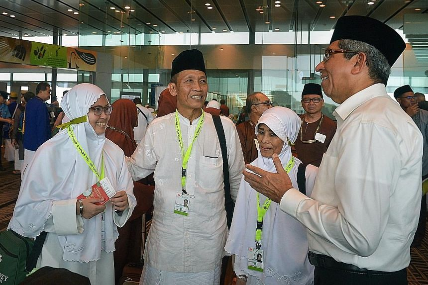 Dr Yaacob Ibrahim with Miss Nur Asyura Suratman (far left), 21, a software engineering technician; her father Suratman Haji Hussein, 60, an oil refinery plant operations supervisor; and mother Hamidah Samsuri, 58, a housewife, before they left on the