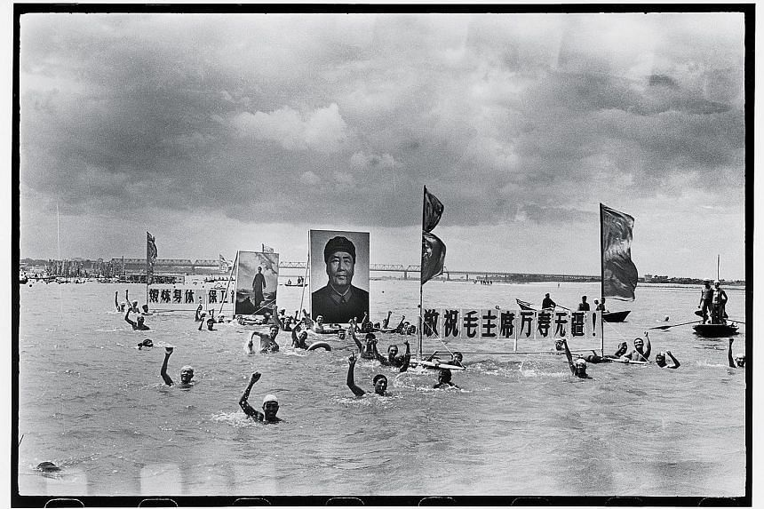 People commemorated the one-year anniversary of chairman Mao Zedong's swim in the Yangtze river by holding his portrait in Songhua River in 1967 (above) - a photograph taken by Li Zhensheng.