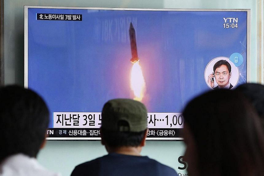 """South Koreans watching a report on the launch of three North Korean missiles on TV in Seoul yesterday. The launch was condemned by the US as """"reckless""""."""