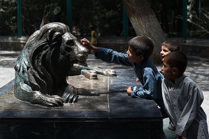 Children petting a statue of Marjan, once the most famous resident at Kabul Zoo - and symbol of Afghan survival. Now, more than a decade after its death, Afghanistan remains battered by war but the zoo is buzzing again and is a welcome refuge for the