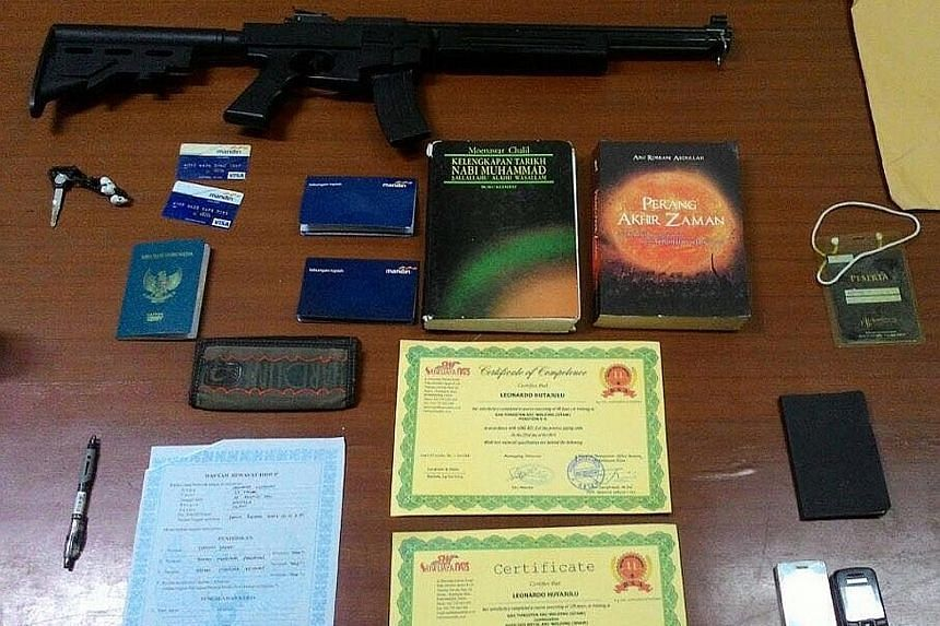 Detachment 88 officers raided the home of the suspect, identified as Leonardus Hutajulu, and seized, among other items, an airsoft replica of an assault rifle, two mobile phones, an Indonesian passport, ATM cards and religious books (above).