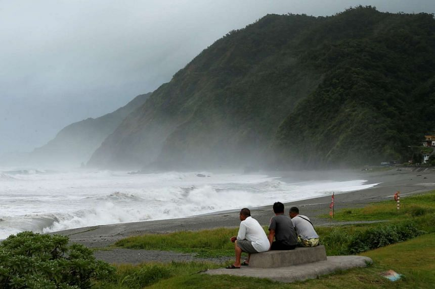 Men watch waves crash at the coast as Typhoon Nepartak approaches in Yilan, Taiwan on July 7, 2016,