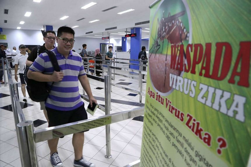 Passengers from a ferry from Singapore walk past a poster warning of the Zika virus at the International Port of Batam Centre, Batam, Riau Islands, Indonesia.