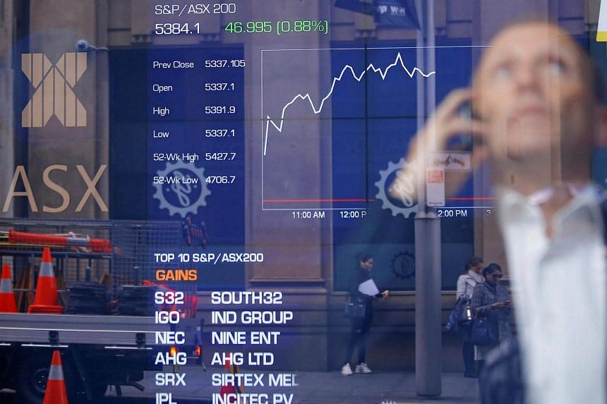 An investor reacts as he talks on his phone in front of a board displaying stock prices at the Australian Securities Exchange in Sydney, Australia on July 12.