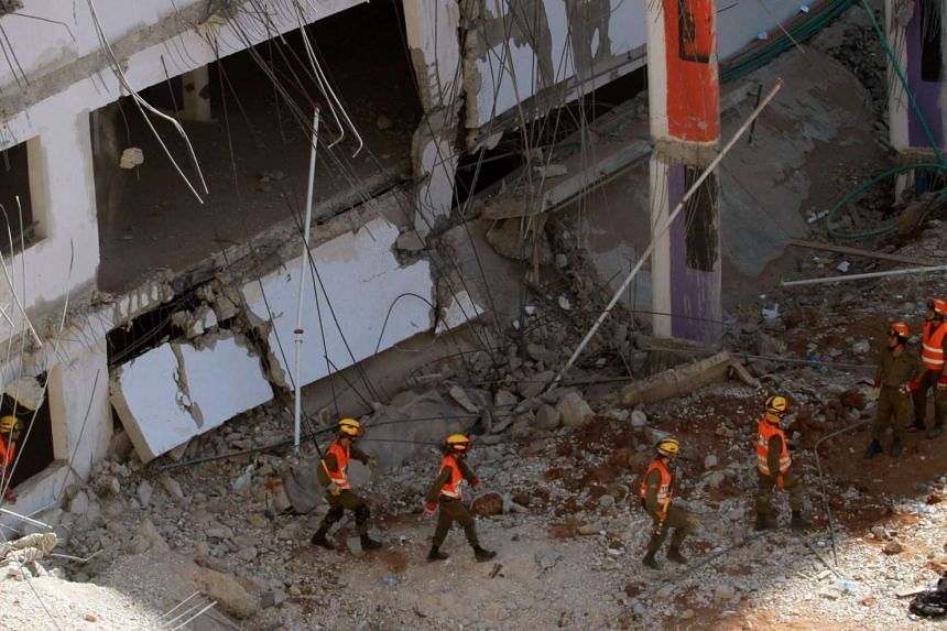 Israeli rescue workers walk at the site where a building collapsed on Sept 5, 2016.