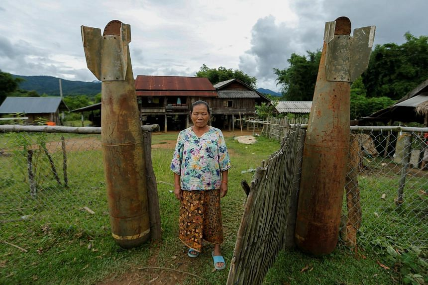 A woman poses at an entrance of her house on Sept 3, 2016, next to bombs dropped by the US Air Force during the Vietnam War.