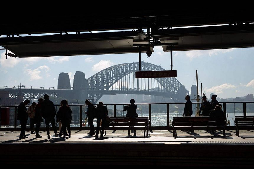 People wait for a train at Circular Quay near the harbour in Sydney on July 5, 2016. Australia's central bank stood pat on interest rates on Tuesday (Sept 6).