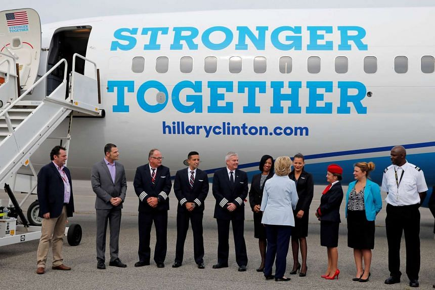 US Democratic presidential nominee Hillary Clinton greets flight crew and others before boarding her newly unveiled campaign plane for the first time at the Westchester County Airport in White Plains, New York.
