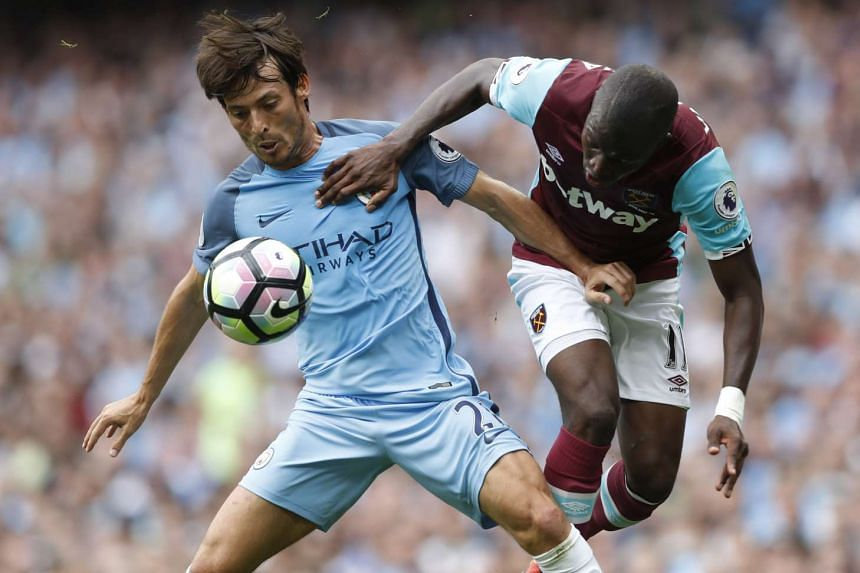 Manchester City's David Silva (left) fighting for the ball with West Ham United's Enner Valencia during their EPL match on Aug 28, 2016.