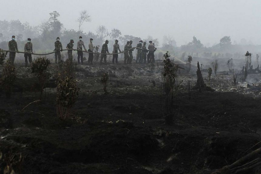 Indonesian police and military personnel working to extinguish fires in Kampar, Riau province, on Aug 29, 2016.