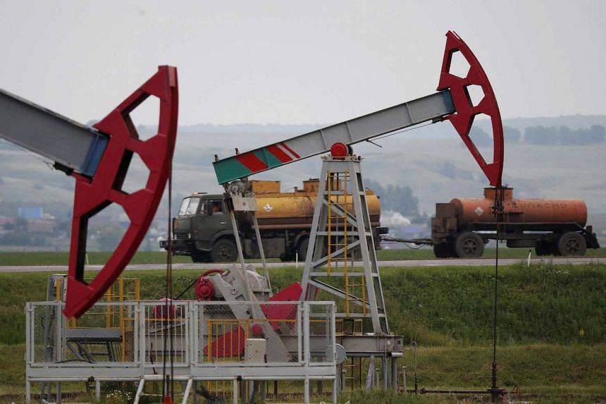 A truck drives past pump jacks at an oil field in Russia.