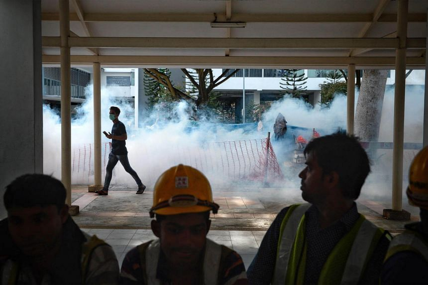 Construction workers watch as fogging goes underway in the morning around Block 401 Bedok North Ave 3 on 1 Sept, 2016.