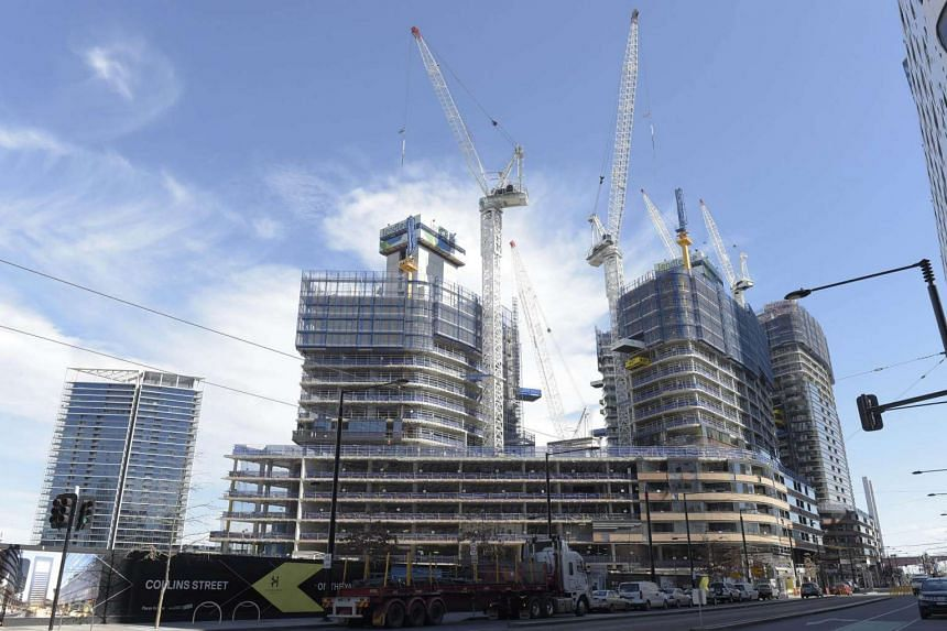 Construction cranes operate above residential towers on a building site in the Docklands area of Melbourne, Australia, on Aug 23, 2016.
