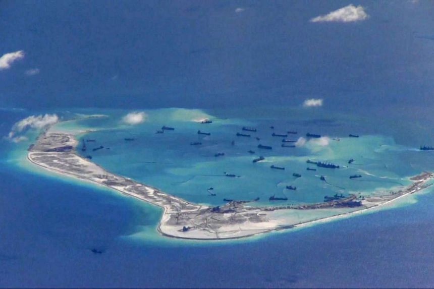 Chinese dredging vessels are purportedly seen in the waters around Mischief Reef in the disputed Spratly Islands in the South China Sea in this still image from video taken by a P-8A Poseidon surveillance aircraft provided by the United States Navy o