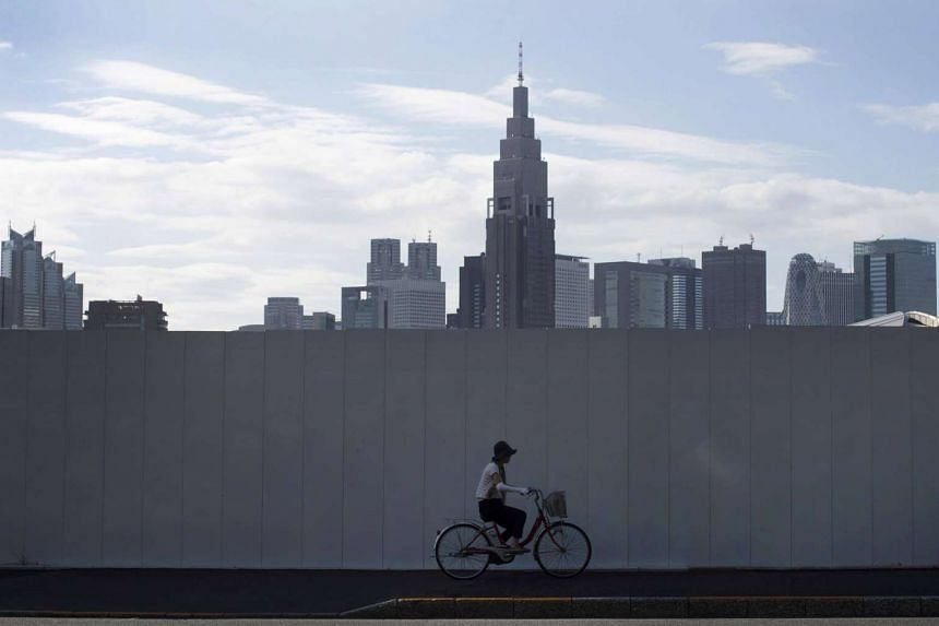 A woman rides a bicycle past the construction site of the new National Stadium as buildings stand behind the site in Tokyo, Japan, on Sept 3, 2016.