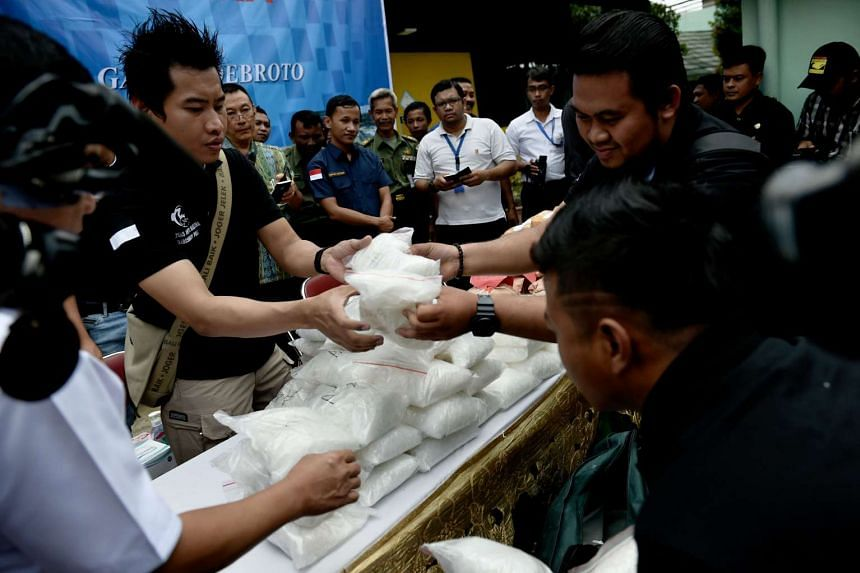 Indonesian anti-narcotics officials and police officers displaying drugs that were seized as evidence, in Jakarta on Sept 7, 2016.