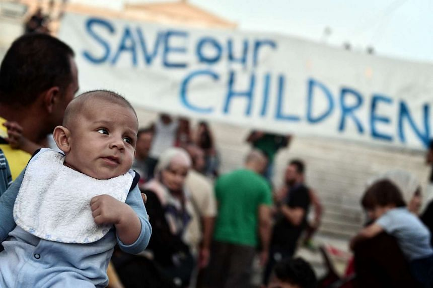 Refugees with their children protest in front of the Greek parliament in Athens on Sept 2, 2016.
