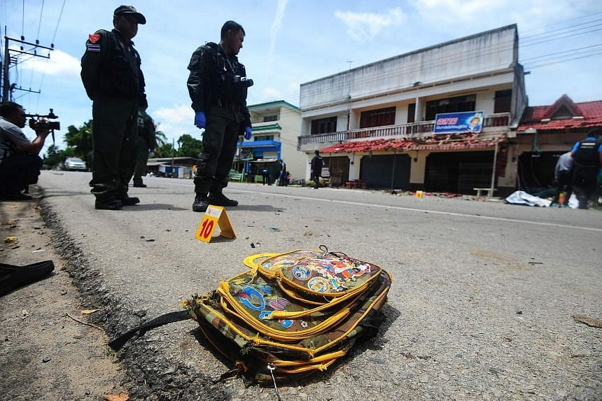 Thai bomb squad members inspecting the site of the motorcycle blast in front of a school in Narathiwat province yesterday.
