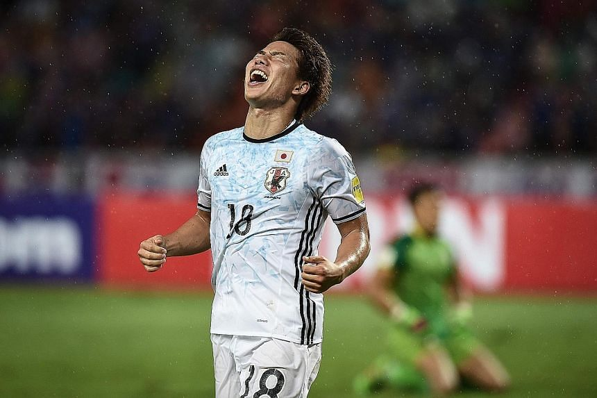 Japan forward Takuma Asano celebrates after scoring against Thailand in a World Cup qualifier yesterday. Japan won 2-0.