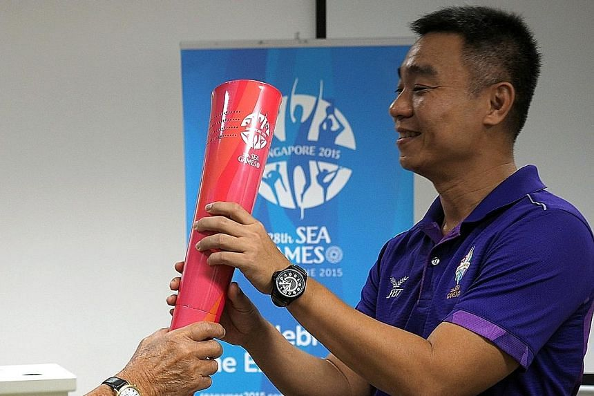 """Toh Boon Yi, holding the SEA Games torch, said his team at the Singapore Sports Institute will help him to """"continue the strong foundation established... and strengthen Singapore's high-performance pathway""""."""