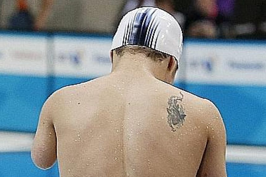 China's Xu Qing celebrates winning the 50m fly S6 final at London 2012. He won four golds in the British capital and has similar targets in Rio. The tattoo on his back (below) shows that he means business.