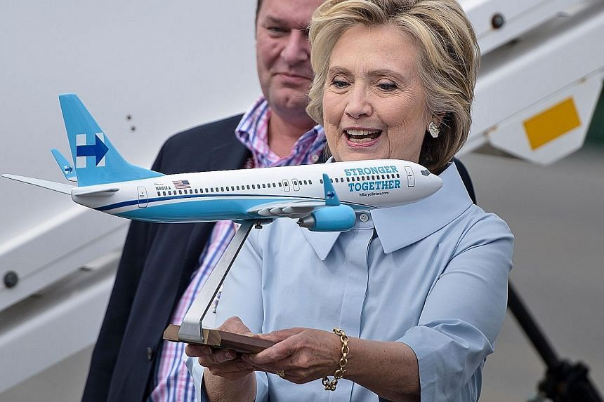 """Mrs Clinton with a model of her new campaign plane at Westchester County Airport before travelling to Ohio on Monday. Her new jet is a Boeing 737-800 that seats about 100 people. It has """"Stronger Together"""" emblazoned along the fuselage and her tradem"""